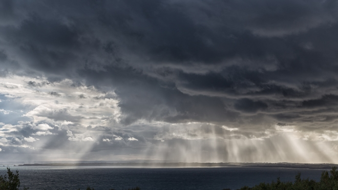 sun-shining-near-dark-clouds-ocean